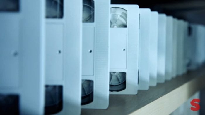 a row of blank white videotapes lined up on a shelf