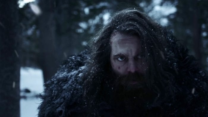 a long haired bearded man sits in the snow