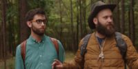 Brian and Jeff hear a sound as they walk through the woods, Jeff puts up his index finger on his right hand instructing Jeff to be still as they both look to their left into the woods.