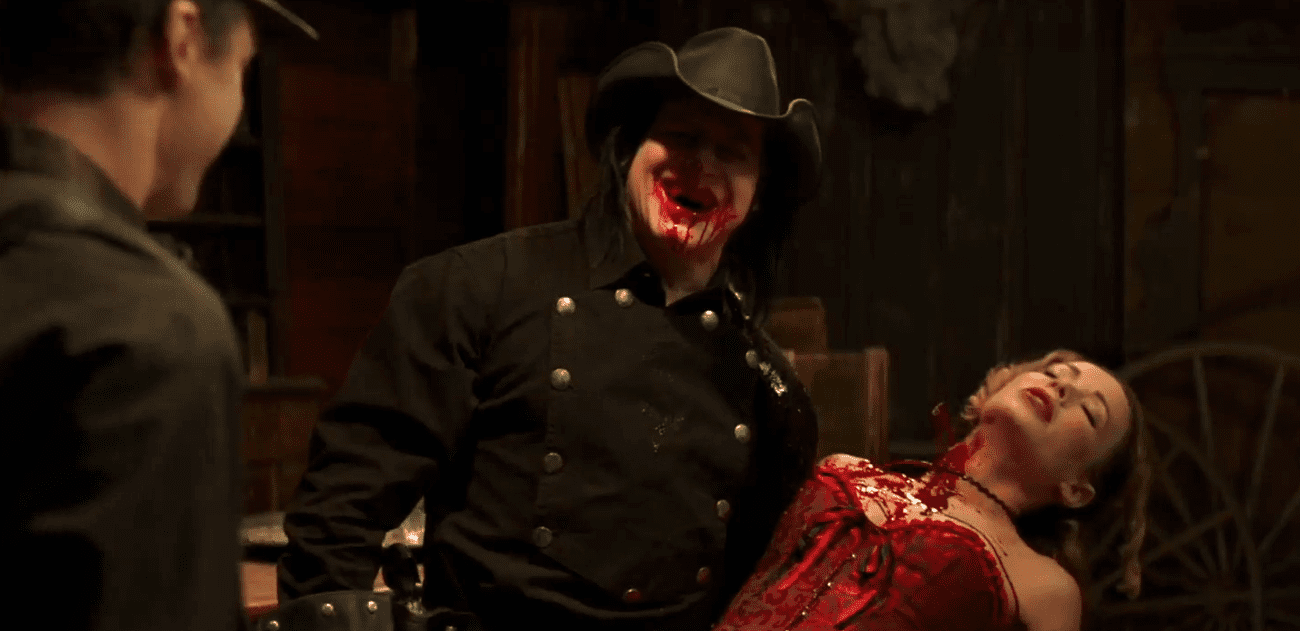 A vampire gives a blood-soaked grin as he holds a scantily-clad unconscious woman with a bloody neck.