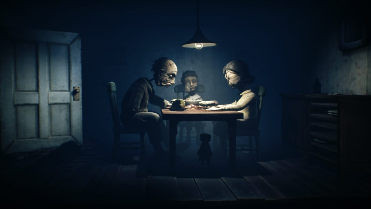 Several people sit at a table. An overhead light illuminates them and casts the rest of the room in darkness. their faces are all disfigured.