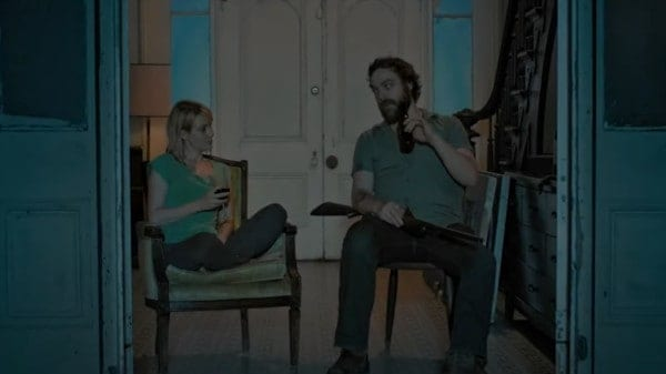 Abby and Hank sit in chairs looking towards the camera. Abby is drinking a glass of wine, Hank, a bottle of beer. He is holding a shotgun