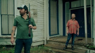 Hank and Wade stand in front of a large house. Hank is wearing a hat and carrying a shotgun.
