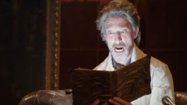 A man opens the Necronomicon and a light shines up from the book as the man stares on with a shocked look on his face