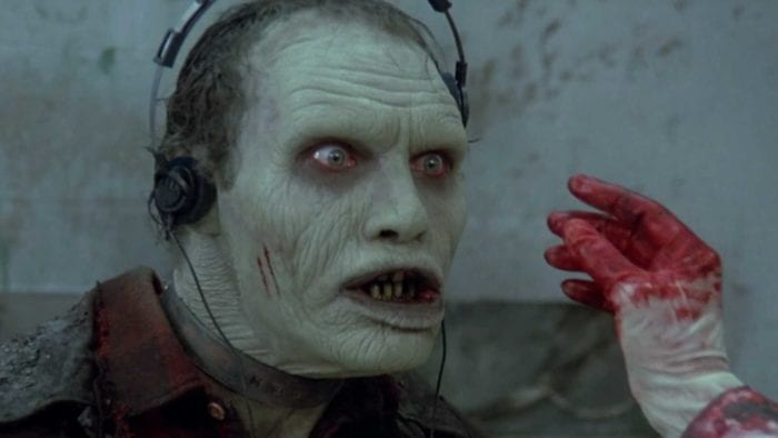 male zombie wearing headphones, a bloody, gloved hand reaches into the frame