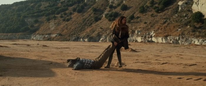 Helena drags a body through a deserted location