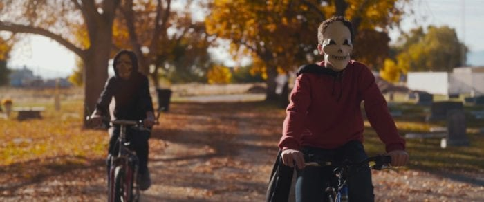 Two costumed kids ride bikes on sunny autumn day