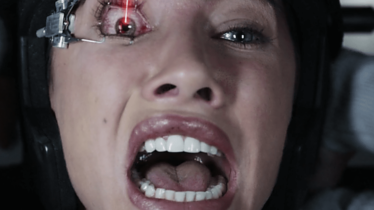 close up of a womans face. she is screaming and a lazer is pointed at her eye