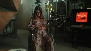A pregant woman sits, holding her stomach in a dark, dingy room.