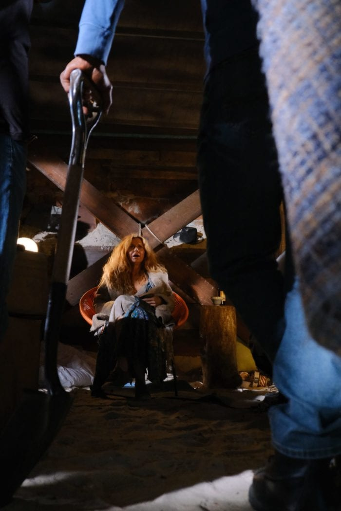 Bree is seen distantly sitting in a beach chair underneath the house between a mans leg and a steel shovel.