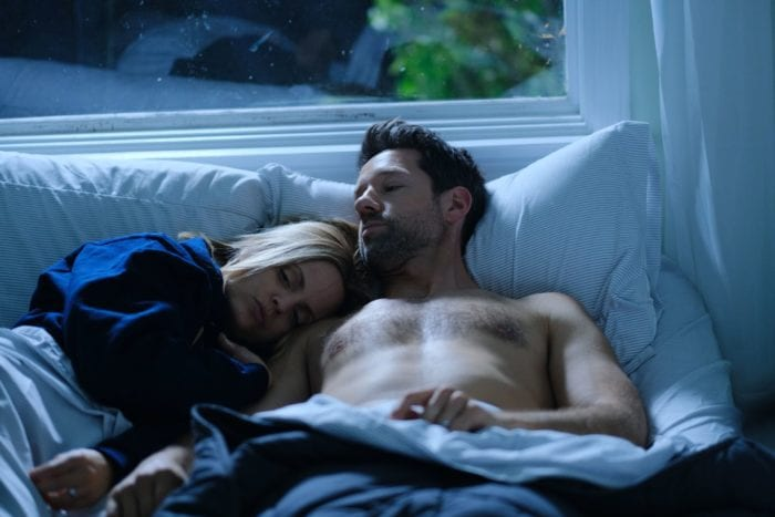Tracey and Knox cuddle in bed under a seaside beach view above them