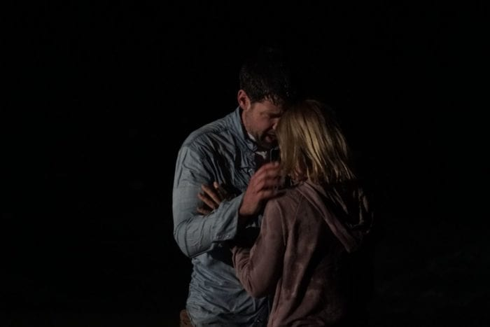 A weathered looking Knox and Tracey share a cautious embrace in the darkness.