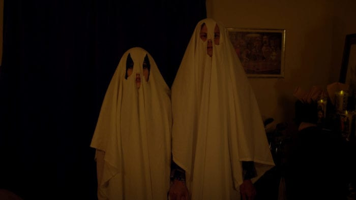 Two people in sheets try to scare the ghosts from their home.