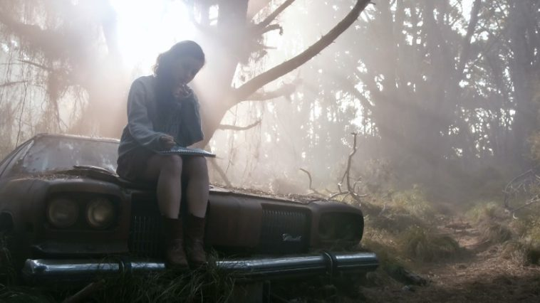 A young woman sits on top of an abandoned car smoking and drawing in a notebook.