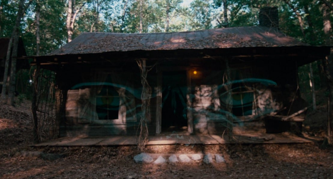 A shot of an old, abandoned looking cabin with a pair of angry looking eyes layered over the image.