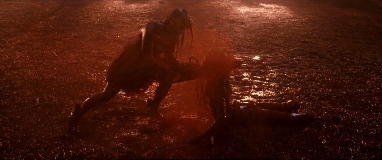 A woman covered in blood is wielding a chainsaw which she is using to cut down a demon that is crawling at her feet.