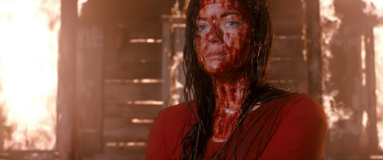 A young woman with blood on her face stands in front of a burning building looking out into the distance.