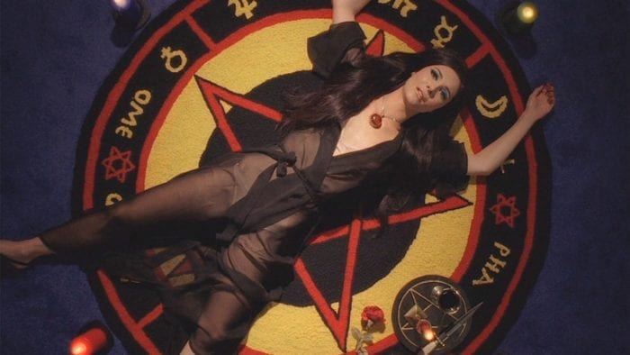 Elaine laying on a pentagram on the floor
