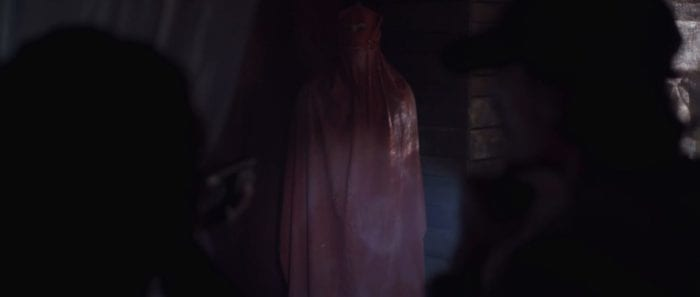 Ivy points a light and a shotgun at a figure dressed in a red hooded cloak in the corner of a cabin