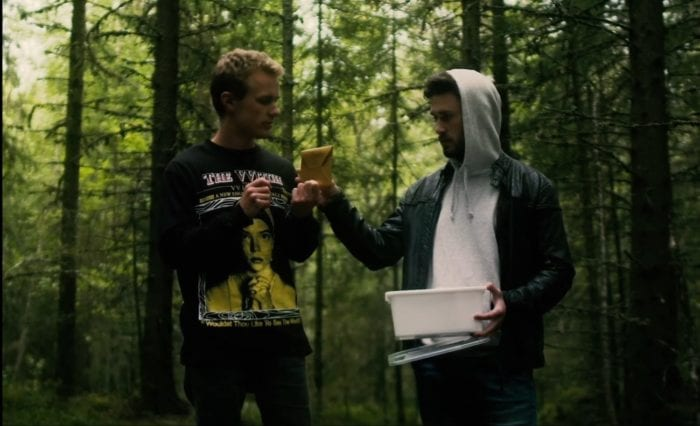 Viljar and Freddy discover the letters in the woods. Viljar holds one letter and Freddy holds the Tupperware box.