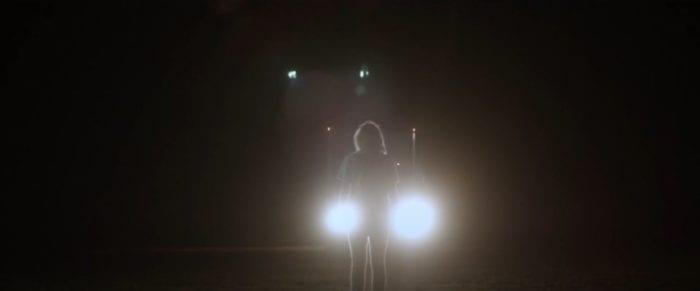 Phoebe stands between the headlights of Dawn's truck.