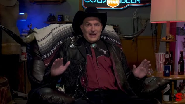 Joe Bob Briggs sits in a chair wearing a cowboy hat and speaking to his audience.