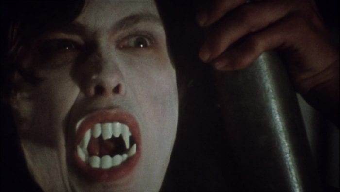 close-up of a pale mans face with a mouth full of plastic vampire fangs