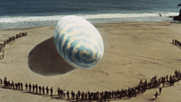 A gaint egg sits in the middle of a beach with hundreds of bystanders staring at it.