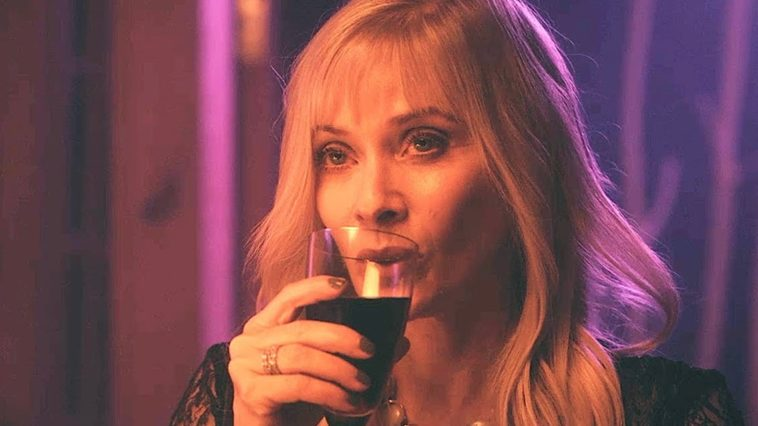 A blonde woman sips a drink out of a glass.