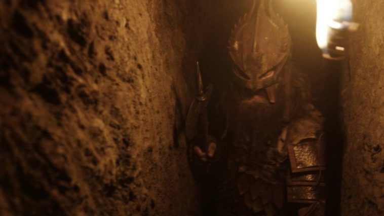 a man in armor walks through a narrow cave, a sword in one hand and a torch in the other