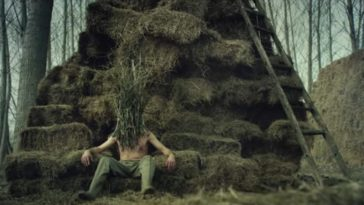 A man wearing trousers and shoes but no shirt has a face covered in grass and twigs and sits on a throne of hay bales. A ladder is propped against it on the right side.