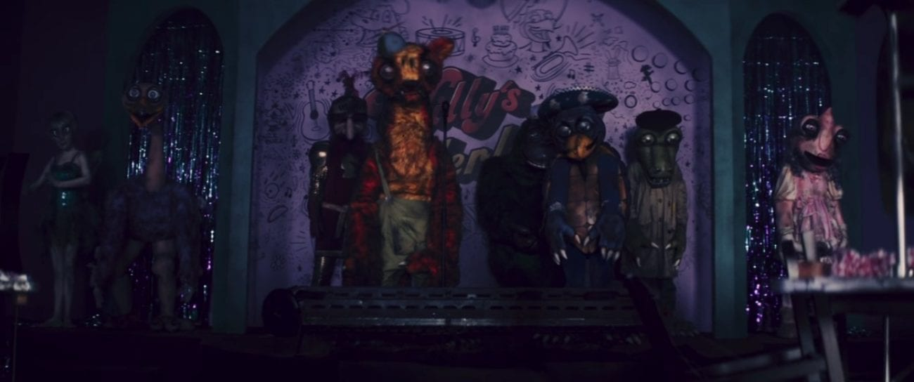 The evil animatronics stand turned off in a dark, dim, and dingy looking room.