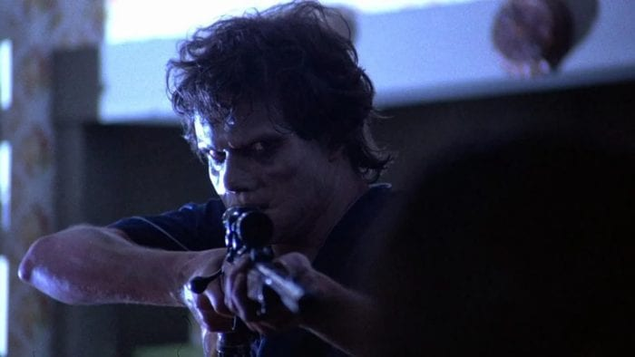 A young man in demonic makeup aims a rifle at the camera.