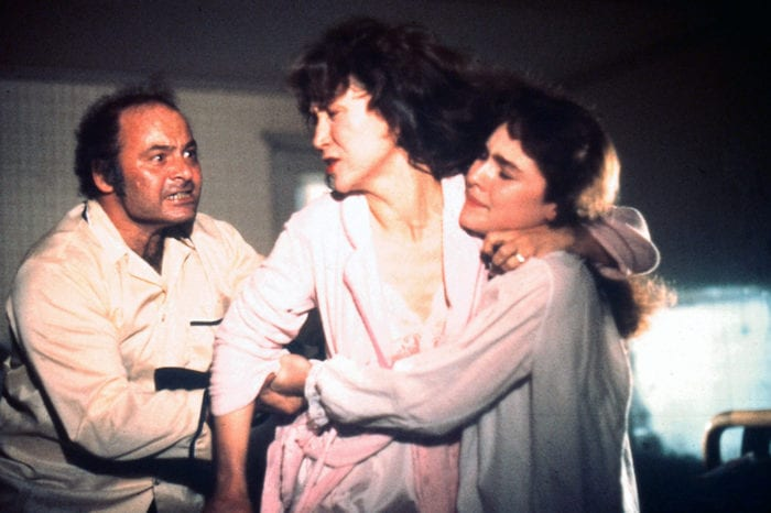 Three people in some sort of conflict. A balding mature man holds a shotgun as he scowls at a woman with a distressed look on her face as a young woman holds her up.