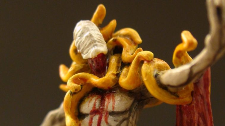 a painted figurine of a mysterious yellow clad figure