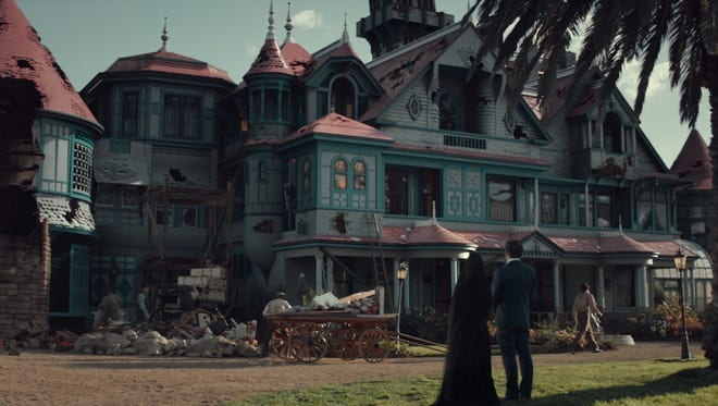 a woman and man stand in front of a spralling mansion
