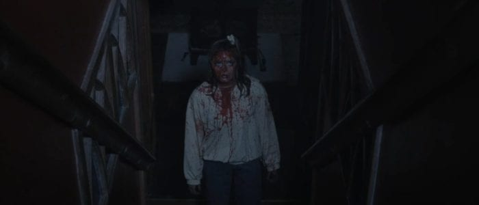 Jamie stands at the base of the stairs covered in blood looking up