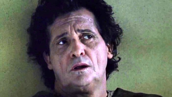 A close up of a disheveled man with a distressed look on his face.