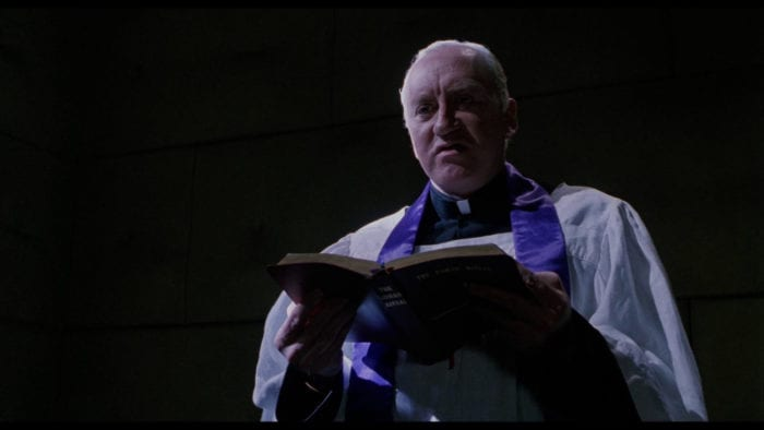 An elderly priest, dressed in his vestments, stands in a dark room reading from a Bible.