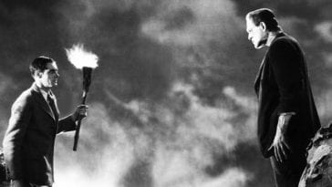 Dr. Frankenstein holds a torch and stands defiantly across from the monster