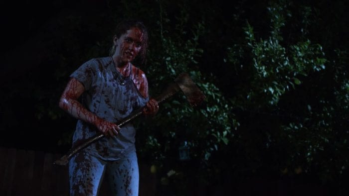 Shelby stands covered in blood holding an axe. The silhouette of a tree next to her.