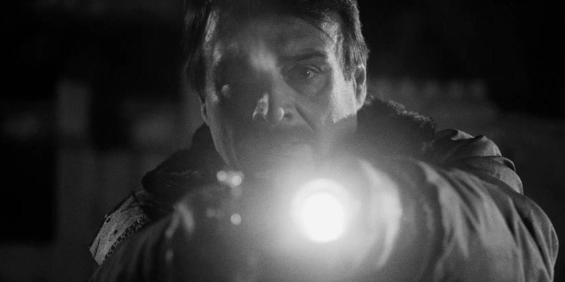 A night watchman points his flashlight and gun at the camera with a shocked look on his face