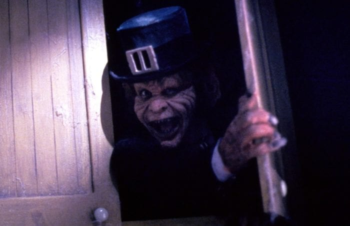 A leprechaun grimaces as he looks out from a wooden cabinet.e