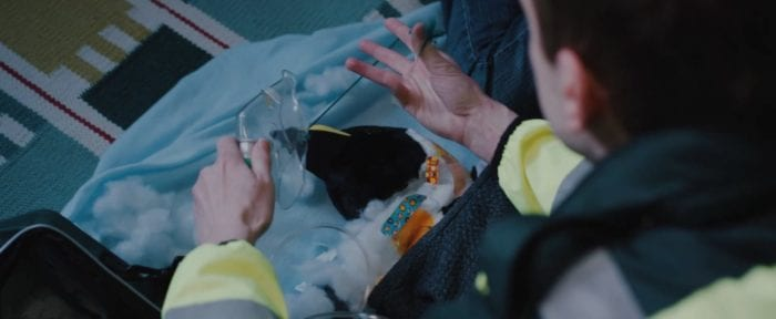 An EMT applies an oxygen mask to Peter the Penguin who's neck is leaking stuffing