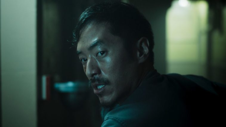 A scared Johnny (Leonard Nam) turns his head in a dark hallway to find something fearful.