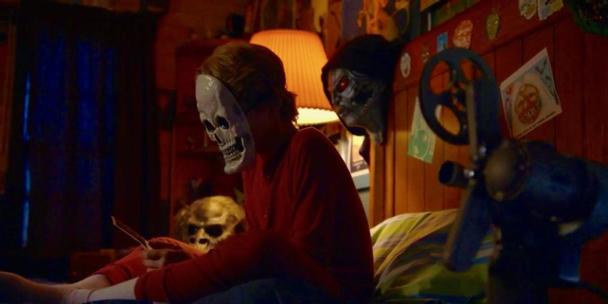 Boy in skeleton mask sits on bed