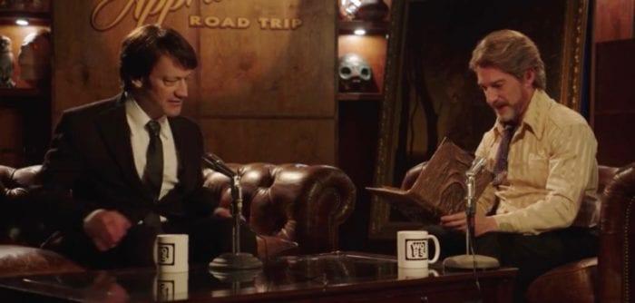 Two men study a book in a tv studio