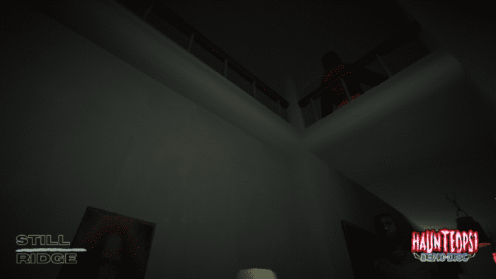 A first person view of a dark house. On the second floor balcony a dark figure in a cloak looms