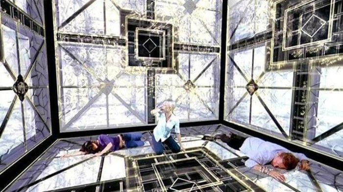 3 people, two woman and a man, are trapped inside a giant cube. the space is brightly lit and there are geometrical shapes on all the walls. one woman sits up while the others lay on the ground unconscious.