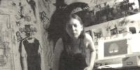 Sophia sits in her room, the walls behind her are covered in drawings of a shadowy figure in a hat